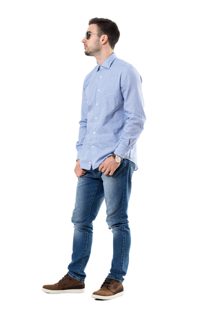 Cool relaxed smart casual young man wearing sunglasses with hands in pockets looking away. Full body length portrait isolated over white background.
