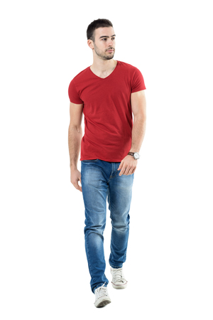 looking towards camera: Young handsome casual man walk towards camera looking away. Full body length portrait isolated over white studio background.
