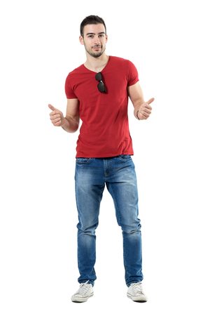 Cool relaxed trendy casual man with thumbs up gesture looking at camera. Full body length portrait isolated over white studio background.