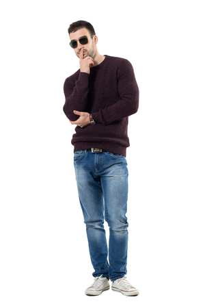 Cool young doubtful  man wearing sweater and sunglasses looking at camera. Full body length portrait isolated over white studio background.