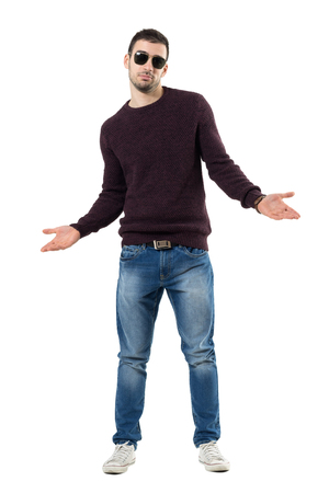 Unsure young man wearing sweater and sunglasses shrugging shoulders. Full body length portrait isolated over white studio background.