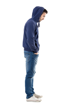 Side view of sad upset man in hooded shirt with hands in pockets looking down. Full body length portrait isolated over white studio background. Stock Photo