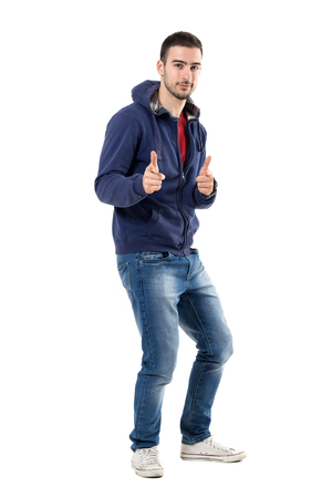 Playful young casual man in sweatshirt with finger gun gesture aiming at camera. Full body length portrait isolated over white studio background.