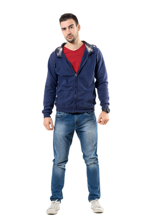 Tense young casual man in blue hooded sweatshirt looking at camera skeptically. Full body length portrait isolated over white studio background.