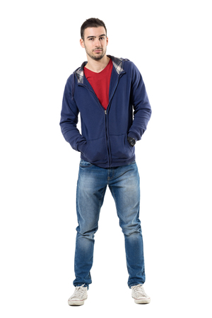 Charming young guy in blue sweatshirt with hands in pockets looking at camera. Full body length portrait isolated over white studio background.