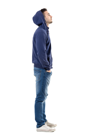 Side view of handsome confident cool young guy with hoodie on head looking up. Full body length portrait isolated over white studio background.
