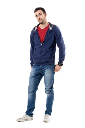 Friendly young handsome guy in blue sweatshirt looking at camera. Full body length portrait isolated over white studio background. Stock Photo