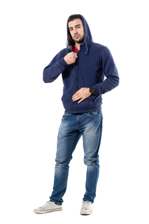 Relaxed young guy fastening zipper on hoodie getting dressed. Full body length portrait isolated over white studio background. Stock Photo