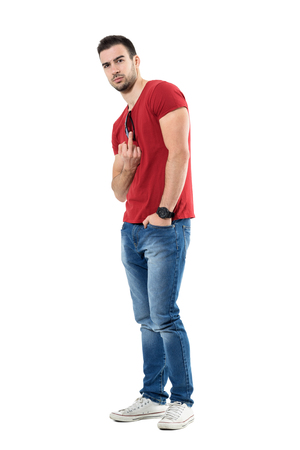 Angry young man wearing jeans and red t-shirt showing obscene middle finger gesture. Full body length portrait isolated over white studio background.