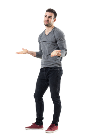Clueless confused young man shrugging shoulders looking away. Full body length portrait isolated over white studio background. Stock Photo