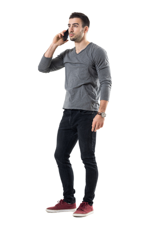 Confident young handsome businessman walking on the phone looking away. Full body length portrait isolated over white studio background.