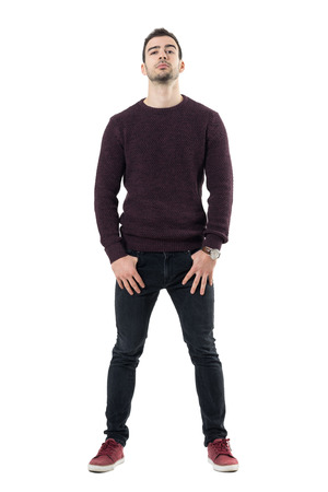 Conceited macho casual man with hands in pockets and head titled back. Full body length portrait isolated over white studio background.