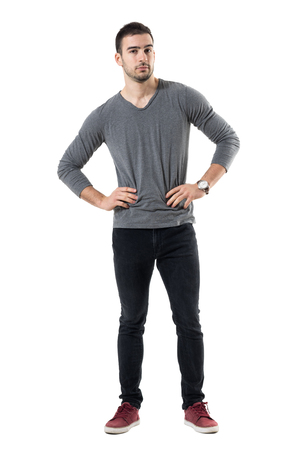 Serious young casual man with hands on waist looking at camera. Full body length portrait isolated over white studio background. Stock Photo