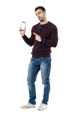 Young smart casual man showing finger advertising blank mobile phone display. Full body length portrait isolated over white studio background.