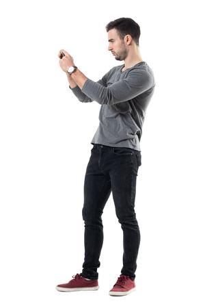 Profili il punto di vista del giovane uomo casuale serio che tiene il cellulare che prende la foto. Ritratto di tutta la lunghezza del corpo isolato su sfondo bianco studio. Archivio Fotografico - 77488978