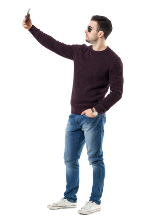 Side view of handsome casual man with sunglasses taking selfie with cell phone. Full body length portrait isolated over white studio background.