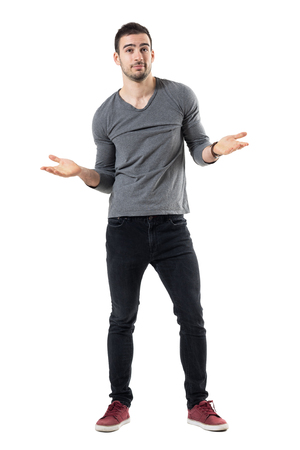 Puzzled young man in gray shirt shrugging with open arms looking up. Full body length portrait isolated over white studio background.