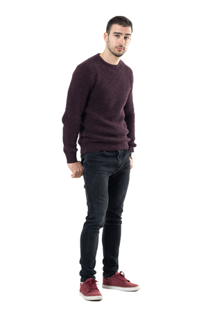 Cool seductive young casual man with hands in back pockets looking at camera. Full body length portrait isolated over white studio background. Stock Photo