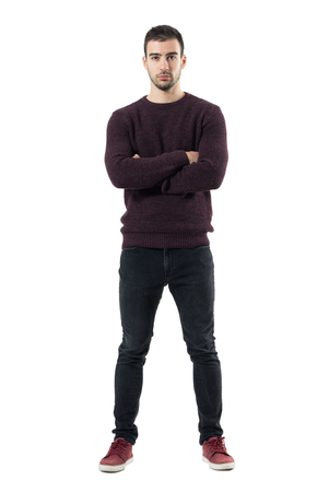 Serious young casual man in maroon sweater with crossed arms looking at camera. Full body length portrait isolated over white studio background. Stock Photo