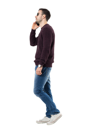 Side view of serious young casual man talking on the phone looking away. Full body length portrait isolated over white studio background. Stock Photo