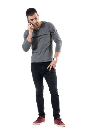 Serious young worried casual man talk on the phone looking down. Full body length portrait isolated over white studio background. Stock Photo