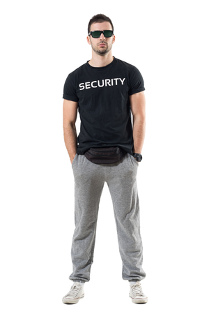 Tough confident macho young undercover cop with hands in pockets looking at camera. Full body length portrait isolated on white studio background. Stock Photo