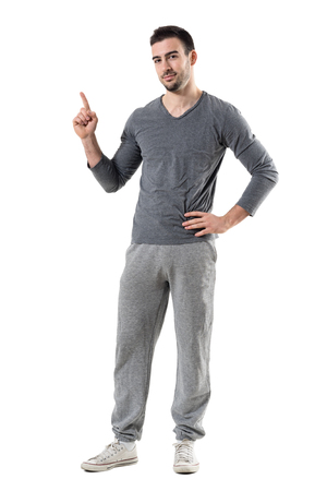 Young fit sporty athlete pointing finger up looking at camera advertising. Full body length portrait isolated on white studio background.