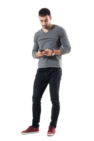 Stylish young trendy man typing message on cellphone. Full body length portrait isolated on white studio background.