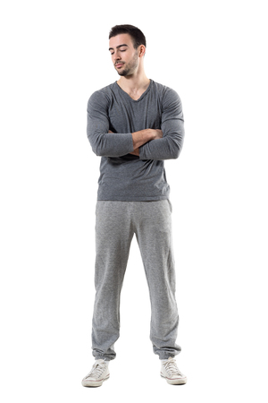 Young fit muscular sporty man with crossed arms looking down. Full body length portrait isolated on white studio background.
