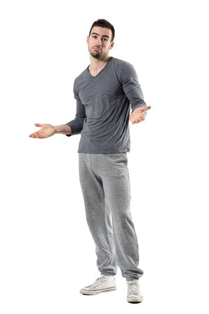 Confused young fit sporty man shrugging shoulders looking at camera. Full body length portrait isolated on white studio background.