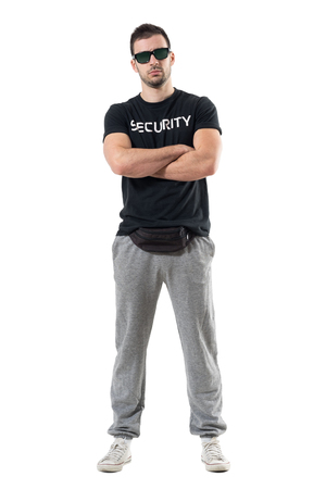 Serious tough macho police man in civil clothes with crossed arms looking at camera. Full body length portrait isolated on white studio background.