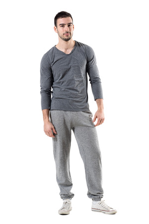 Cool relaxed fit man in sportswear looking at camera. Full body length portrait isolated on white studio background.