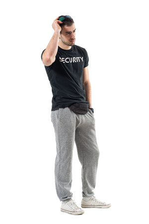 Young sporty security guard with fanny bag holding sunglasses looking away. Full body length portrait isolated on white studio background.