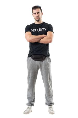 Stoere machobeschermer die tailletas met gekruiste wapens draagt die camera bekijken. Het volledige portret van de lichaamslengte dat op witte studioachtergrond wordt geïsoleerd.