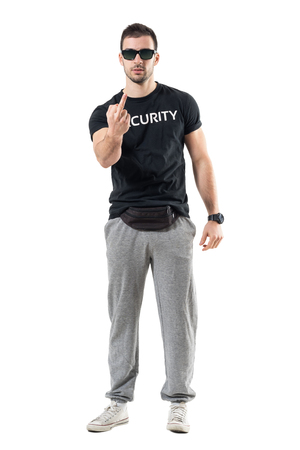 Rude bodyguard or bouncer showing middle finger obscene gesture at camera. Full body length portrait isolated on white studio background.