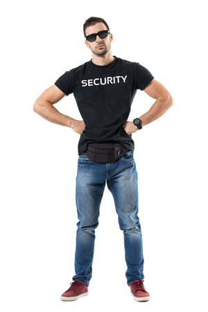Serious macho bouncer or undercover officer with hands on hips looking at camera. Full body length portrait isolated on white studio background.