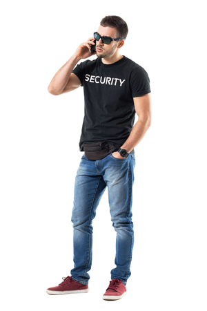 Frustrated young undercover police officer talking on the mobile phone. Full body length portrait isolated on white studio background.