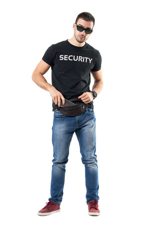 Undercover policeman in plain clothes put mobile phone in waist bag. Full body length portrait isolated on white studio background.