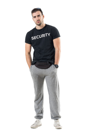 Skeptical young bouncer with hands in pockets frowning and looking at camera. Full body length portrait isolated on white studio background. Stock Photo