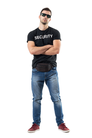 Macho bouncer or undercover cop in plain clothes looking at camera with crossed arms. Full body length portrait isolated on white studio background.