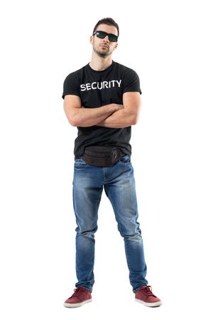 Machobuitsproeier of geheime agent in gewone kleding die camera met gekruiste wapens bekijkt. Het volledige portret van de lichaamslengte dat op witte studioachtergrond wordt geïsoleerd. Stockfoto