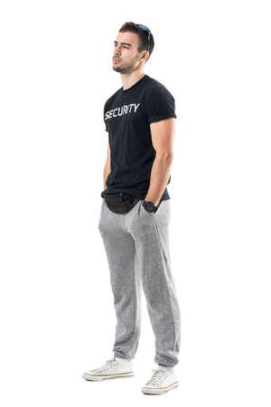 Side view of fit masculine sporty man with hands in pockets looking away. Full body length portrait isolated on white studio background.