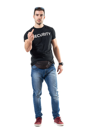 guardaespaldas: Rude police officer in civilian plain clothes showing middle finger gesture at camera. Full body length portrait isolated on white studio background. Foto de archivo
