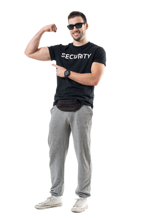 Fit young man in sportswear with fanny pack showing flexing bicep arm muscle. Full body length portrait isolated on white studio background.