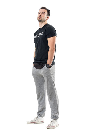 Side view of young macho bouncer with hands in pocket and head tilted back. Full body length portrait isolated on white studio background.