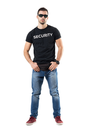 Undercover policeman holding fanny pack belt looking at camera with sunglasses. Full body length portrait isolated on white studio background. Reklamní fotografie