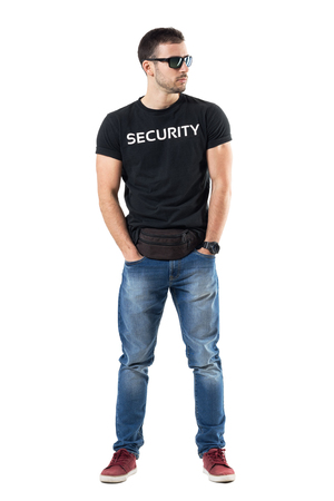 Undercover police officer in plainclothes with hands in pockets looking away. Full body length portrait isolated on white studio background.