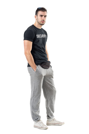 Profile view of suspicious skeptical young muscular bouncer staring at camera. Full body length portrait isolated on white studio background.