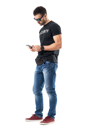 Side view of young undercover policeman typing message on mobile phone. Full body length portrait isolated on white studio background. Stock Photo