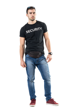 Serious confident young plainclothes officer with fanny pack looking at camera. Full body length portrait isolated on white studio background. Stock Photo
